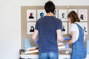 Two students looking at an art wall with self portraits