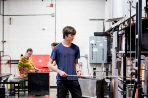 Summer Arts Studio participant works in the hot shop