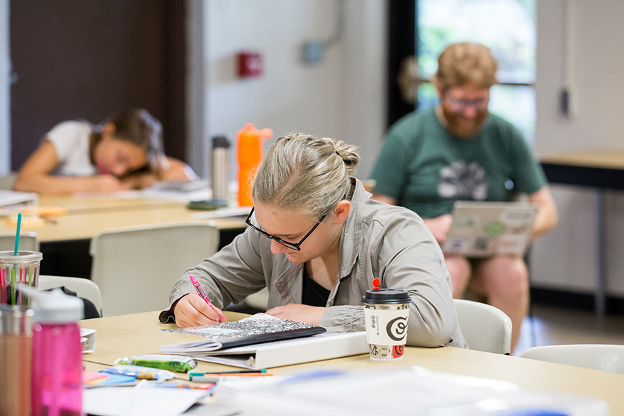 Student writing at a table during a Rise Up And Write Event
