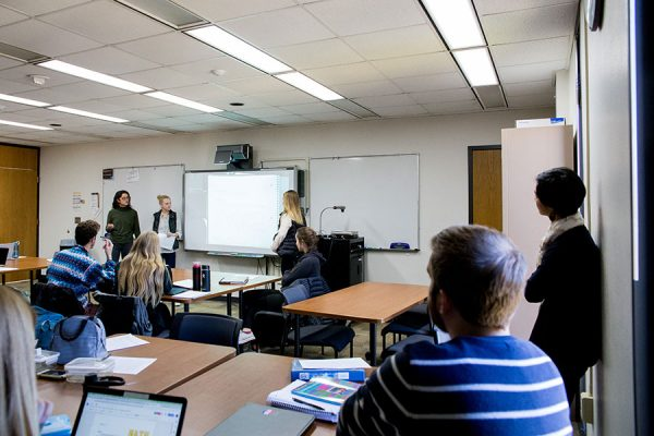 Students and teachers in a classroom giving a presentation