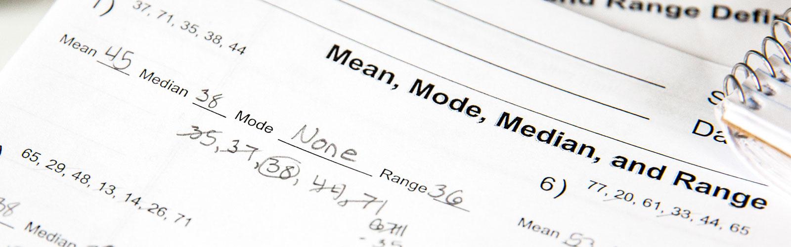 Close-up of a math worksheet on mean, median, mode, and range