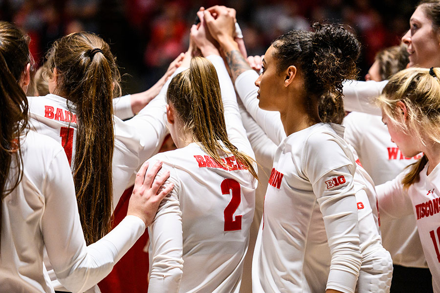 UW–Madison Women's Volleyball team raising their hands together