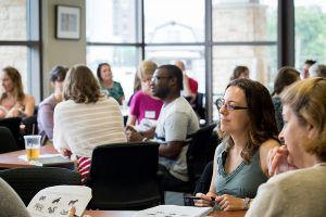 A group of educators sit around a table and listen to a speaker during an academic conference.
