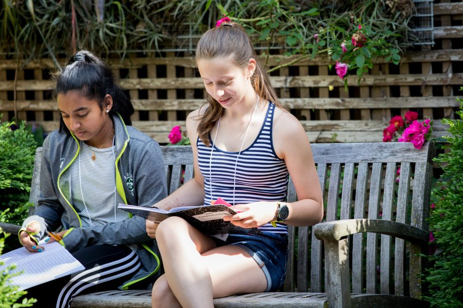 Twio students writing on a bench