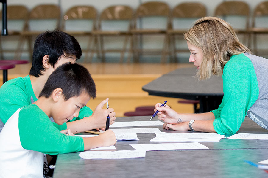 Teacher working with students at a table