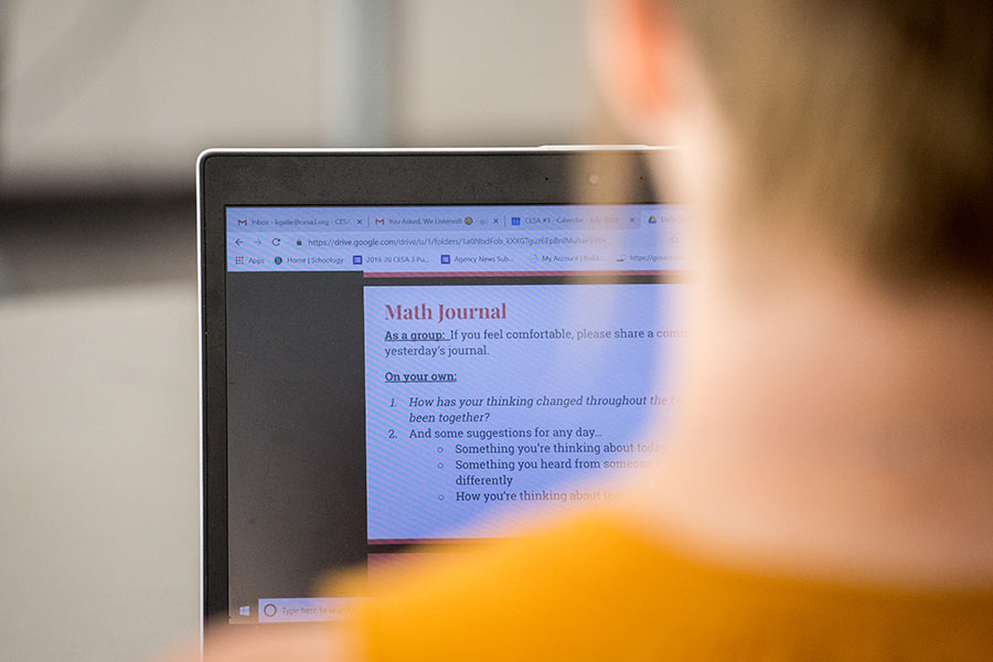 person in front of laptop screen looking at a Math Journal