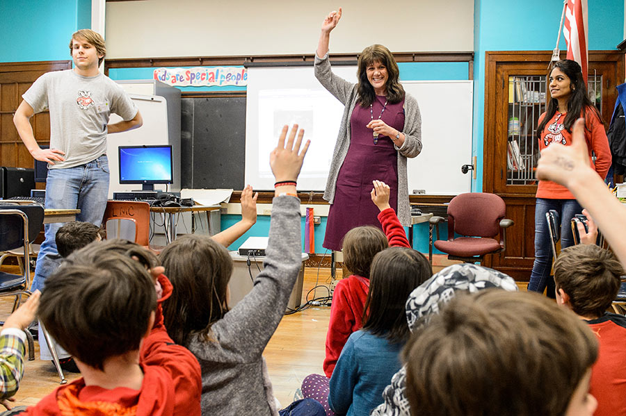 An instructional coach stands in front of a group of elementary school students who are seated on the floor and raising their hands.