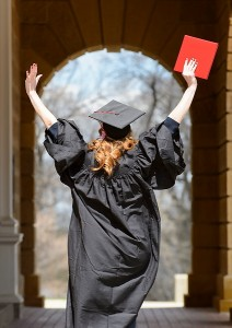 Graduating student walking through an archway
