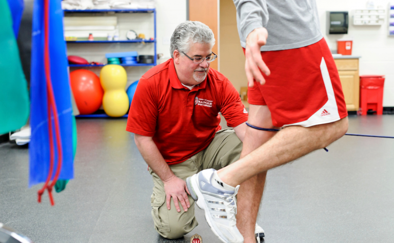 Clinical Preceptor Enrique Perez-Guerra works with an athlete in the Kohl Sports Medicine facility.