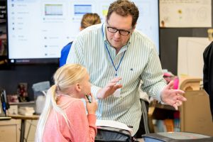 UW–Madison student teacher in a classroom assisting a student