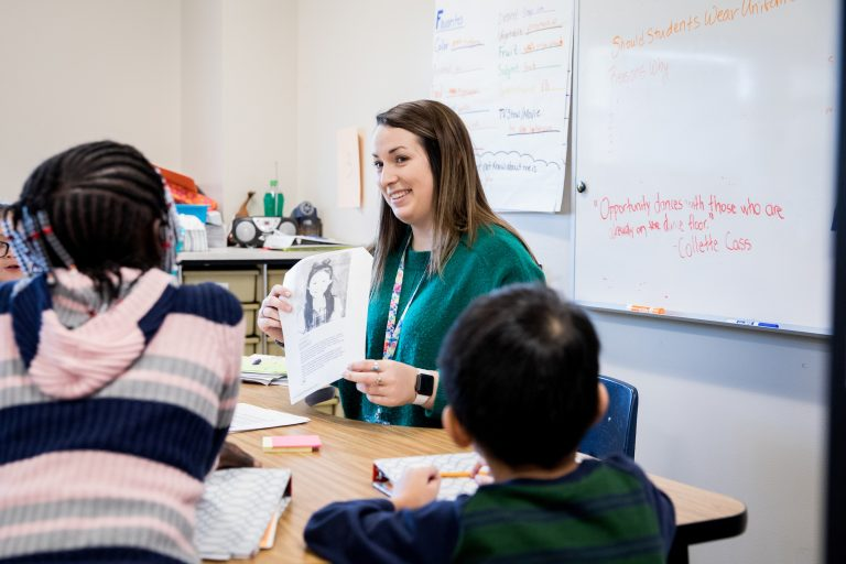 Student teacher holding a paper and talking to two young students.
